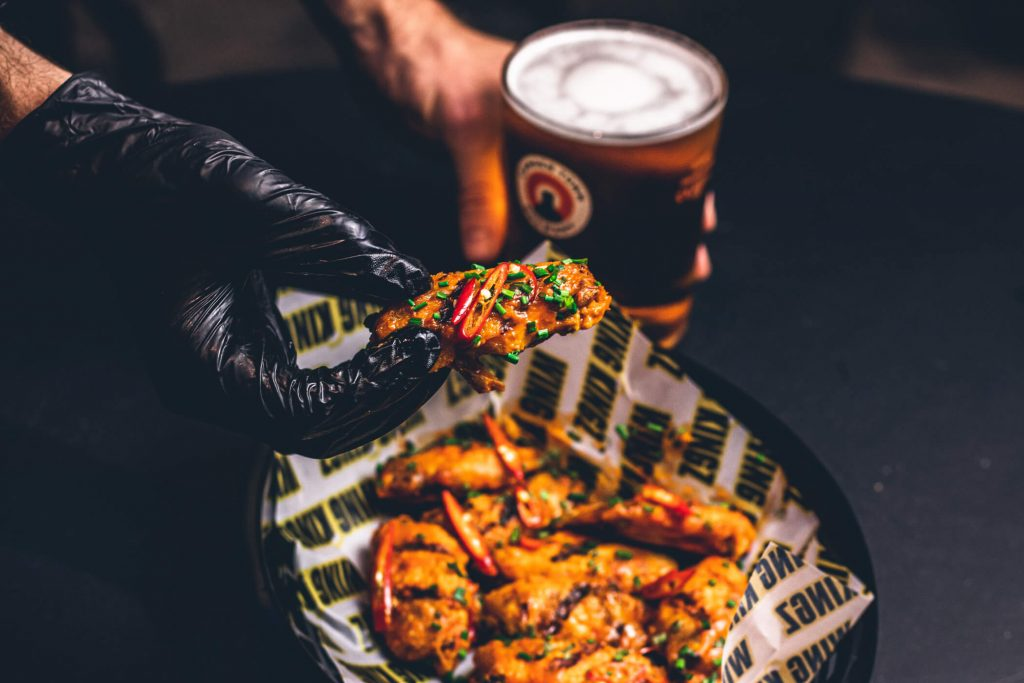 Hand holding wings with beer